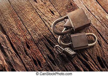 Old padlocks on grunge wooden background.