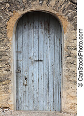Old painted blue door on the stone wall.