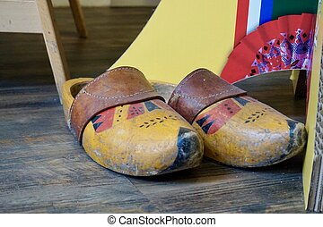 Old painted Dutch wooden clogs with a leather strap, on th floor of a tourist shop, next to a display stand. A bit of the cardboard fo the display stand shows. Painted in yellow, red and black.