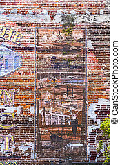 old painted pictures at the brick wall