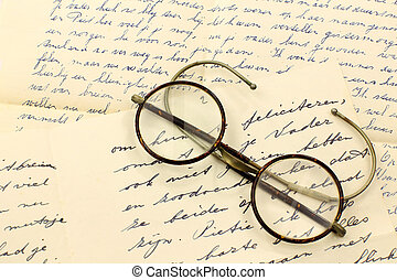 old pair of glasses on some letters