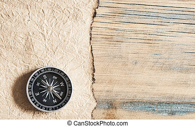 old paper and compass on a wooden table