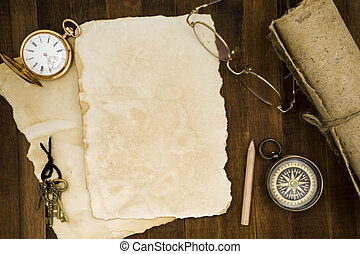 Old paper, compass, pocket watch on wooden background