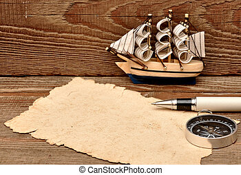 old paper, compass, rope and model classic boat on wood background