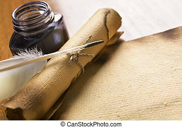 Old paper, scroll and quill on wooden table