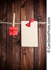 old paper sheet with bow and small gift box hanging on...