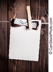old paper sheet with bow hanging on clothesline against...