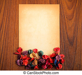 old paper with dry flower on wooden background