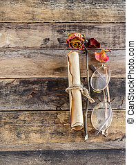 Old paper with dry rose on wooden background