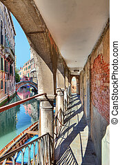 Old passage along canal. Venice, Italy.