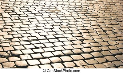 Old paving stones texture. Road surface and sunlight.