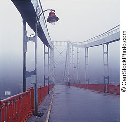 Old pedestrian bridge in Kiev in the early morning mist, the lone passer goes to work