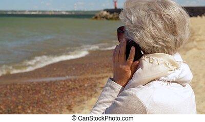 senior woman calling on smartphone on summer beach - old...