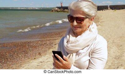 senior woman using smartphone on summer beach - old people...