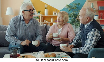 Old people friends talking drinking tea doing high-five sitting at table with food