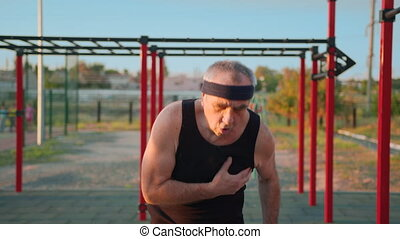 Old people healthy lifestyle. Elderly caucasian man making fitness exercises after coronavirus virus pandemic in playground. Workout for senior people. Athletic old grandfather.