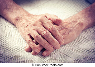 Care is at home of elderly. Old people holding hands closeup. Elderly man.