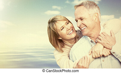 Two aged smiling people over sky background