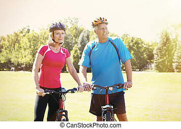 Two aged people with bycicle over park background