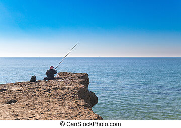Old person fishing - old person fishing in the edge of the...