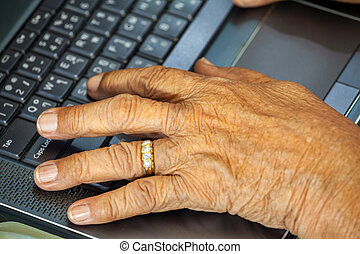 Old person hands typing on a keyboard