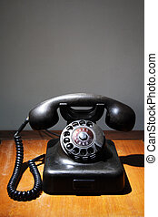 An old black rotary phone on a table