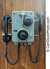 Old phone hanging on a wooden wall