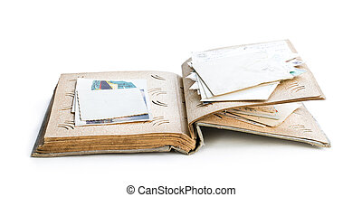 Old photo album with photos and post cards isolated on white