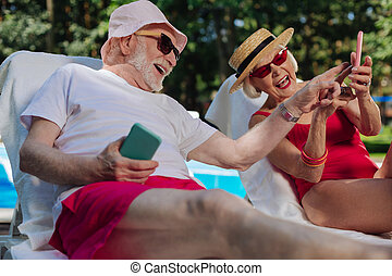 Modern retired man and woman watching old photos on phones