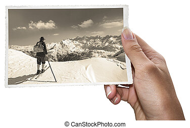 A woman holding old photos of skier with traditional old wooden skis
