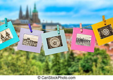 Old photos of the main landmark of Prague in a fun framework, attached with a clothes-peg clothespin to the hanging lashing rope against the backdrop of the panorama of Prague.
