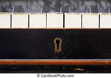 Old piano keys close up with keyhole