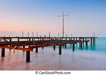 Old pier in the sea at dawn