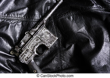 Old military pistol on black leather background