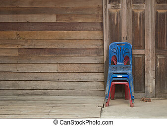 Old Plastic chairs isolated on wooden wall background and wooden floor.