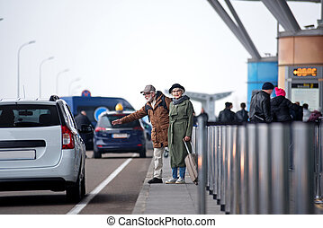 Old pleasant man and woman are stopping car