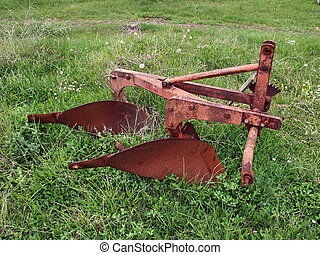 Old plough on the grass, view