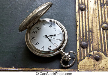 Old pocket watch on vintage background