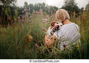 old pointer dog and owner posing together in the meadow in summer