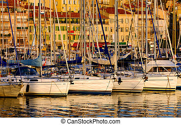 The Vieux Port (old port) in the city of Cannes in the French riviera, as the first rays of the morning sun illuminate the marina and the buildings behind the boats.