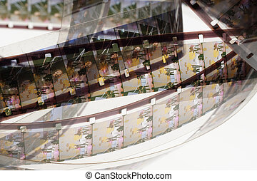 Old positive 16 mm film strip on white background, strip of tangled movie film - place for copy and space text