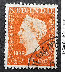 THE NETHERLANDS CIRCA 1948 Old Dutch Indies postage stamp with image of Queen wilhelmina commemorating her 50 years on the throne. The Dutch Indies were a colony of the Netherlands for hundreds of years and are now known as Indonesia.