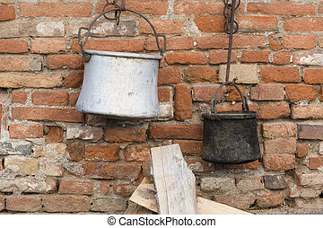 old pots and pans hanging on wall