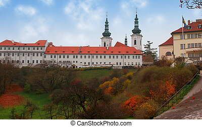 Old Prague cloister on hill with beautiful trees in park under bright blue clouds sky background