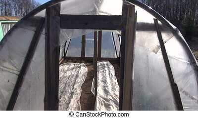 old primitive greenhouse hothouse in early spring after...