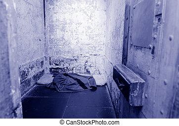 Empty old prison cell interior.