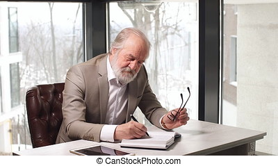 Old professor with grey hair and beard in beautiful suit...