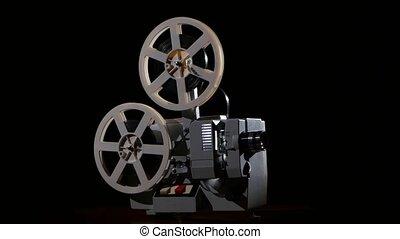 Old projector showing film. Studio black background