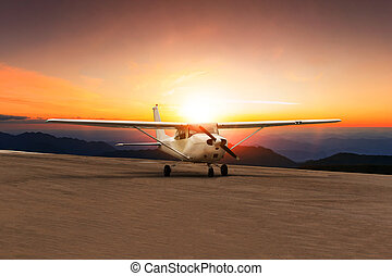 old propeller plane taxi on airport runway against beautiful sun set sky