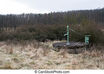 Old pump with leafless forest, water shortage scarcity concept